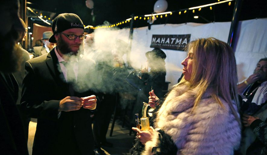 Partygoers smoke marijuana during a Prohibition-era themed New Year's Eve invite-only party celebrating the start of retail pot sales, at a bar in Denver, in this Dec. 31, 2013, file photo. Colorado is on the brink of becoming the first state with licensed pot clubs. Denver officials are working on regulations to open a one-year pilot of bring-your-own marijuana clubs. (AP Photo/Brennan Linsley, File)