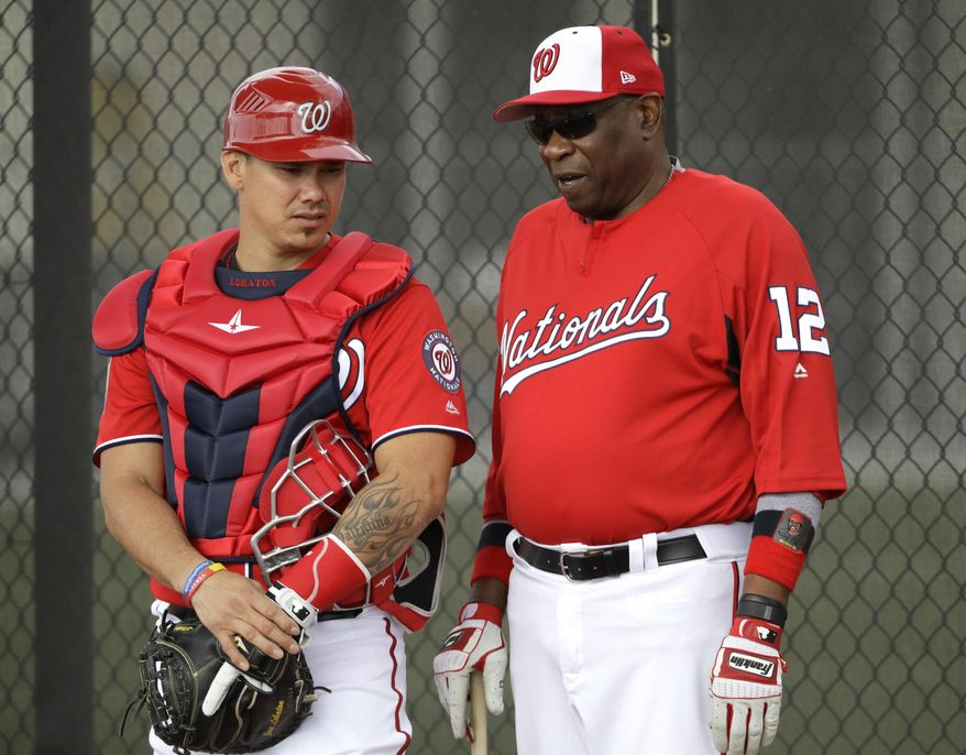 Washington Nationals manager Dusty Baker (12) talks with catcher Jose Lobaton during a spring training baseball workout Thursday, Feb. 16, 2017, in West Palm Beach, Fla. (AP Photo/David J. Phillip)