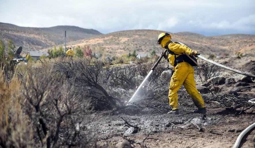 FILE - In this Oct. 14, 2016, file photo, a firefighter hoses down the area on Mount Rose Highway and Edmonton Drive in Reno, Nev. An investigation into a prescribed burn that sparked a northern Nevada wildfire that destroyed 23 homes found several questionable practices on the part of the Nevada Division of Forestry, including understaffing despite an understanding that unstable weather conditions made for a potentially dangerous situation.(Mike Higdon/The Reno Gazette-Journal via AP, File)