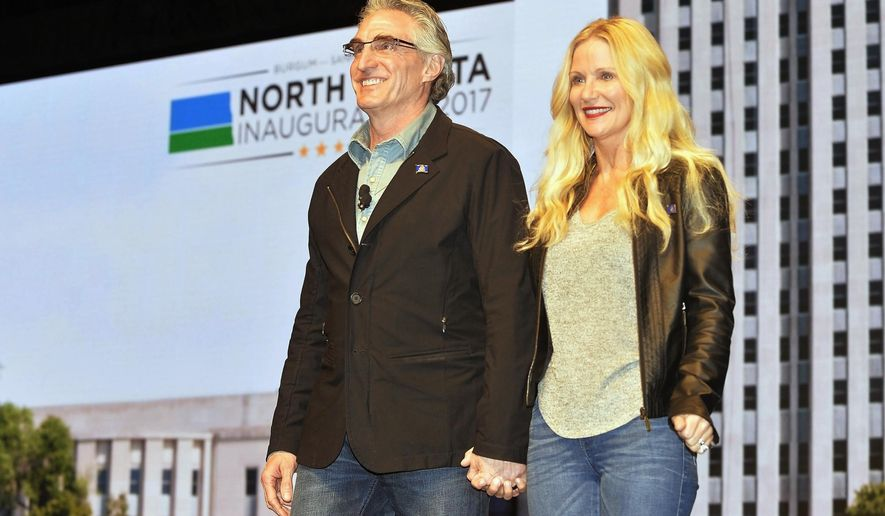 """FILE - In this Jan. 4, 2017 photo, North Dakota Gov. Doug Burgum and first lady Kathryn Helgaas Burgum greet the crowd at the governor's inauguration celebration in Bismarck, N.D. Burgum's preference for wearing jeans got him booted from the North Dakota Senate floor Wednesday, Feb. 15, 2017, while he was posing for a photo with some high school students. A spokesman says the governor """"meant no disrespect to the chamber rules."""" (Will Kincaid/The Bismarck Tribune via AP, File)/The Bismarck Tribune via AP)"""