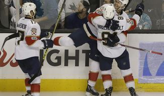 Florida Panthers left wing Jonathan Huberdeau, top, celebrates with center Jonathan Marchessault (81) and center Derek MacKenzie (17) after scoring a goal in overtime against the San Jose Sharks in an NHL hockey game in San Jose, Calif., Wednesday, Feb. 15, 2017. The Panthers won 6-5. (AP Photo/Jeff Chiu)