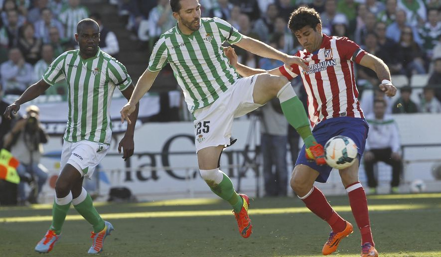 FILE - In this March 23, 2014 file photo, Betis' Jordi Figueras, center, fights for the ball with Atletico de Madrid's Diego Costa, right during their La Liga soccer match at the Benito Villamarin stadium, in Seville, Spain. A Spanish judge has charged three former players of first-division club Real Betis Amaya Carazo, Jordi Figueras and Xavi Torres and former directors of Osasuna for their alleged involvement in match fixing three years ago after court documents were released Thursday Feb. 16, 2017. (AP Photo/Angel Fernandez, File)