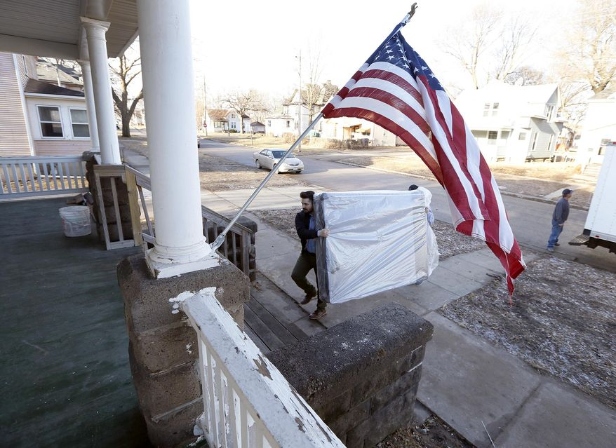 In a Tuesday, Feb. 14, 2017 photo, Chris Jung, left, and Jeff Carlson, both with Slumberland Furniture, unload new mattresses donated by Slumberland to the Americans For Independent Living Veterans house in Waterloo, Iowa. The homeless shelter for veterans is expected to be open this month, thanks to donations from several sources. (Brandon Pollock/The Courier via AP)