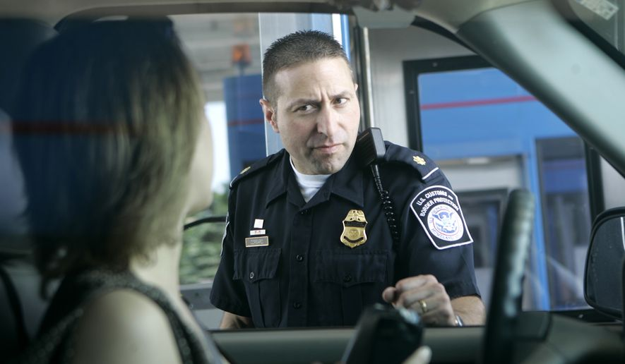 U.S. Customs and Border Protection officer Kevin Corsaro speaks with an unidentified motorist entering the United States from Canada at the border in Buffalo, N.Y., on June 6, 2006. (Associated Press) **FILE**