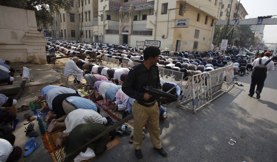 A Pakistani police officer stands guard during a Friday's prayers in Karachi, Pakistan, Feb. 17, 2017. Pakistani forces killed and arrested dozens of suspects in sweeping raids overnight and into Friday, a day after a massive suicide bombing by the Islamic State group killed dozens of worshippers at a famed Sufi shrine in the country's south. (AP Photo/Fareed Khan)