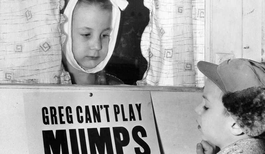 FILE - In this Jan. 16, 1957 file photo, Jon Douglas, 6, right, visits his friend, Greg Cox, standing behind a sign warning he has mumps, on the door of his home in Altamont, Ill. Fifty years ago, mumps was once a childhood rite of passage of puffy cheeks and swollen jaws. That all changed with the arrival of a vaccine in the late 1960s, and mumps nearly disappeared. But in 2017, the U.S. is in the midst of one of the largest surges in decades. (AP Photo)