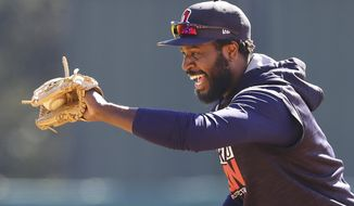 Atlanta infielder Brandon Phillips is all smiles fielding a grounder at the teams spring training facility in Lake Buena Vista, Fla., Friday, Feb. 17, 2017.  (Curtis Compton/Atlanta Journal-Constitution via AP)