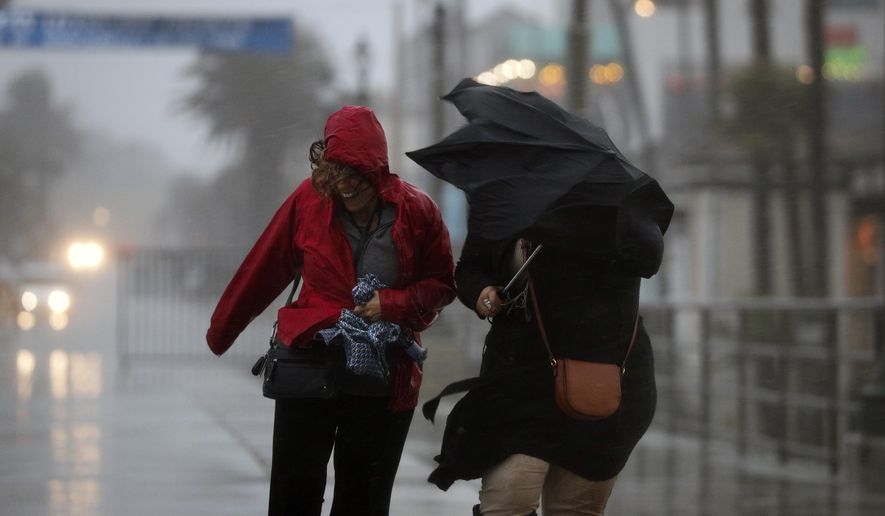 Rita Maissno, right, and Lara Seltzer make their way through heavy rain and gusty wind as they walk along a pier Friday, Feb. 17, 2017, in Huntington Beach, Calif. A major Pacific storm has unleashed downpours and fierce gusts on Southern California, triggering flash flood warnings and other problems. (AP Photo/Jae C. Hong)