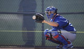Chicago Cubs catcher Miguel Montero catches a ball during a spring training baseball workout Tuesday, Feb. 14, 2017, in Mesa, Ariz. (AP Photo/Morry Gash) **FILE**