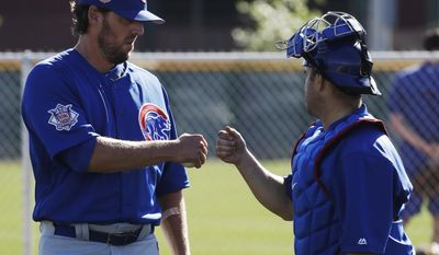 Chicago Cubs catcher Miguel Montero congratulates pitcher John Lackey after throwing during a spring training baseball workout Tuesday, Feb. 14, 2017, in Mesa, Ariz. (AP Photo/Morry Gash)