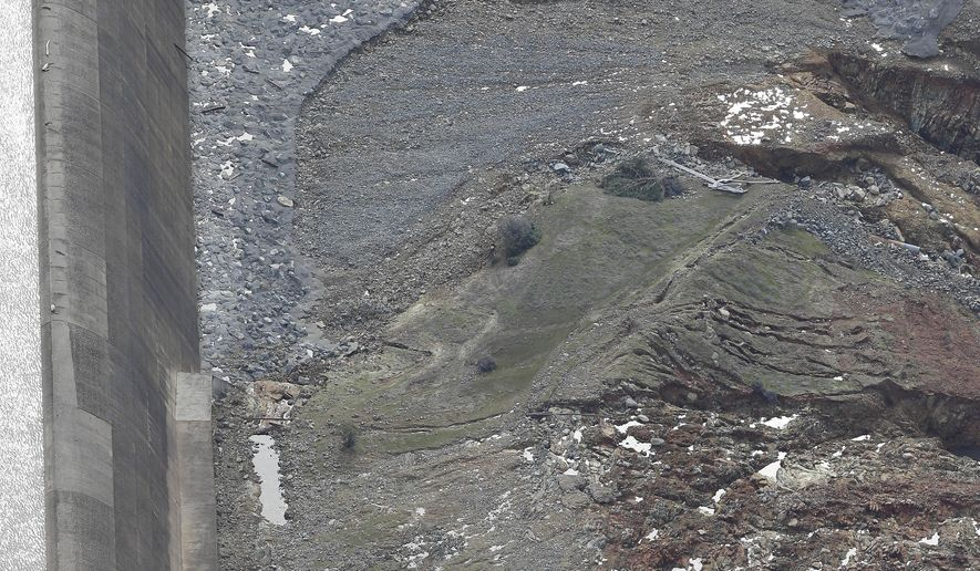 This photo taken Monday, Feb. 13, 2017, shows erosion caused when overflow water cascaded down the emergency spillway, right, of the Oroville Dam in Oroville, Calif. Water flowed over the emergency spillway Sunday morning when Lake Oroville reached capacity, and engineers determined the hillside was eroding faster then expected, undermining the concrete wall. Officials fearing it was about to collapse ordered thousands of residents downstream to evacuate. (AP Photo/Rich Pedroncelli)