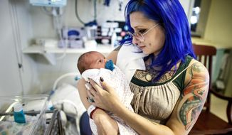 ADVANCE FOR USE SATURDAY, FEB. 18 - In this Feb. 7, 2017 photo, Logan Keck, 23, of Carlisle, holds her daughter, born Feb. 1, in the NICU unit at Holy Spirit-Geisinger in East Pennsboro Township, Pa. Keck was initially addicted to heroin and was in recovery for two years on methadone maintenance treatment when she found out she was pregnant. Keck's baby is now on morphine to help her through withdrawal. (Dan Gleiter/PennLive.com via AP)