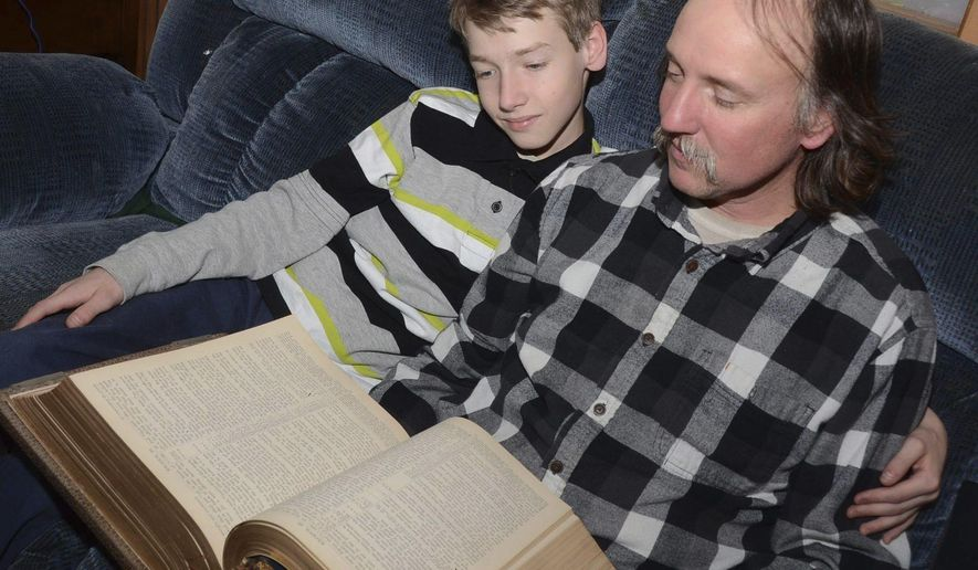 In this February 2017 photo, Peter Hildebrand sits with his father Duane Hildebrand as they read the Bible at their home in Sugarloaf, Pa. (Ellen F. O'Connell /Hazelton Standard-Speaker via AP)