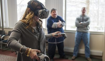 In this Friday, Feb. 10, 2017 photo, Amy Williams, a teacher at Elizabeth Forward Middle School, practices with a virtual reality set during a class at the Allegheny Intermediate Unit in Homestead, Pa. (Nate Smallwood /Pittsburgh Tribune-Review via AP)