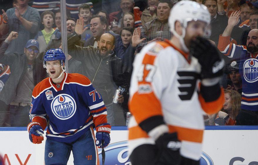 Philadelphia Flyers defenseman Andrew MacDonald (47) skates past as Edmonton Oilers defenseman Oscar Klefbom (77) celebrates a goal during the second period of an NHL hockey game Thursday, Feb. 16, 2017, in Edmonton, Alberta, (Jason Franson/The Canadian Press via AP)