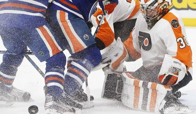 Philadelphia Flyers goalie Michal Neuvirth (30) looks for the rebound during the second period of the team's NHL hockey game against the Edmonton Oilers on Thursday, Feb. 16, 2017, in Edmonton, Alberta, (Jason Franson/The Canadian Press via AP)