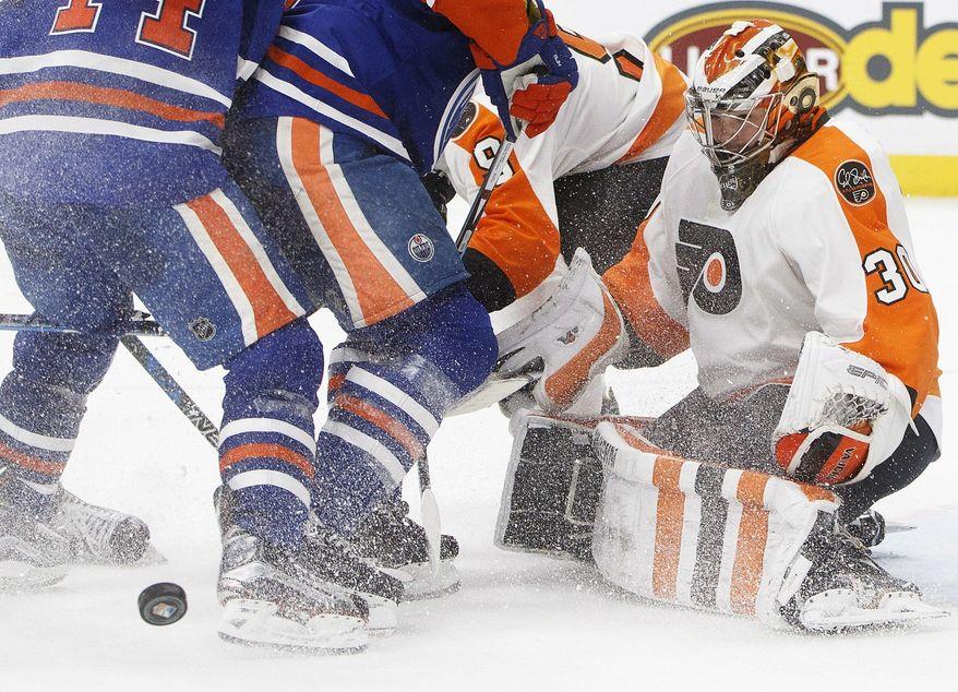 Philadelphia Flyers goalie Michal Neuvirth (30) looks for the rebound during the second period of the team's NHL hockey game against the Edmonton Oilers on Thursday, Feb. 16, 2017, in Edmonton, Alberta, (Jason Franson/The Canadian Press via AP)