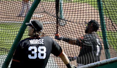 Eduardo Nunez hits as teammate Michael Morse (38) looks on during the San Francisco Giants' spring training baseball workout, Friday, Feb. 17, 2017, in Scottsdale, Ariz. (AP Photo/Matt York)