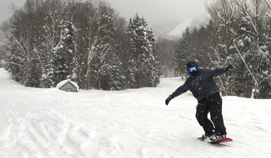 In this Thursday, Feb. 16, 2017 photo, a snowboarder makes their way down a run at Burke Mountain Resort in East Burke, Vt. Following a snow deprived winter last season, Mother Nature has answered the call of skiers and snowboarders in northern New England, dumping mounds of snow in recent days. (AP Photo/Lisa Rathke)