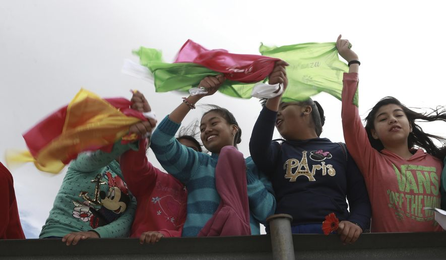 "Young people wave colored flags reading ""Peace"" as they form a symbolic human wall along the Rio Grande, which marks the border between Mexico and the U.S. in Ciudad Juarez, Friday, Feb. 17, 2017. Responding to plans by President Donald Trump to build a wall along the length of the U.S.-Mexico border, more than a thousand people lined the Mexican bank of the Rio Grande in Ciudad Juarez Friday, holding hands and carrying flowers.(AP Photo/Christian Torres)"