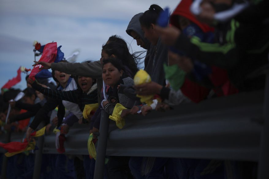 """Young people hold colored flags reading """"Peace"""" as they form a symbolic human wall along the Rio Grande, which marks the border between Mexico and the U.S. in Ciudad Juarez, Friday, Feb. 17, 2017. Responding to plans by President Donald Trump to build a wall along the length of the U.S.-Mexico border, more than a thousand people lined the Mexican bank of the Rio Grande in Ciudad Juarez Friday, holding hands and carrying flowers.(AP Photo/Christian Torres)"""