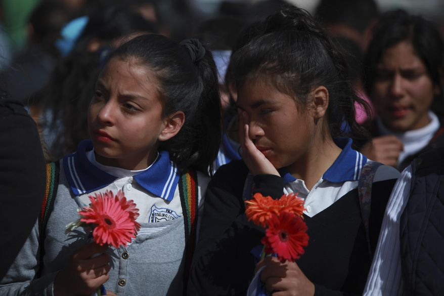 Mexicans students stand together as they form a symbolic human wall along the Rio Grande, which marks the border between Mexico and the U.S. in Ciudad Juarez, Friday, Feb. 17, 2017. Responding to plans by President Donald Trump to build a wall along the length of the U.S.-Mexico border, more than a thousand people lined the Mexican bank of the Rio Grande in Ciudad Juarez Friday, holding hands and carrying flowers.(AP Photo/Christian Torres)