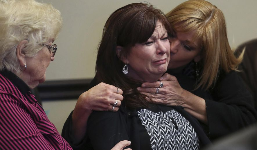 FILE - In this Jan. 23, 2015, file pool photo, Susan Hunt, center, shed tears while surrounded by family during a court appearance in Saratoga Springs, Utah. Hunt, whose son was shot by police while holding a costume samurai sword, has settled a lawsuit over his death, resolving a conflict with her onetime lawyer that reached a federal appeals court. (Spenser Heaps/The Daily Herald via AP, Pool, File)