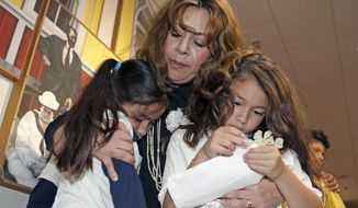 Nora Sandigo Otero, right, comforts Yardley Vanegas, left, and Sherley Ramirez, right, children under her legal guardianship, as they leave the Miami-Dade County hearing, Friday, Feb. 17, 2017, in downtown Miami. Sandigo Otero, who is legal guardian to around 1,000 American-born children and minor teenagers who at least one of their parents has been deported, is asking the Miami-Dade commissioners to reverse Mayor Carlos Gimenez's position on immigration that requires local police to work with federal officers to enforce immigration law. (AP Photo/Alan Diaz)
