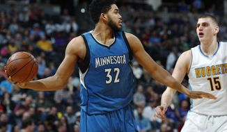 Minnesota Timberwolves center Karl-Anthony Towns, left, pulls in a rebound as Denver Nuggets forward Nikola Jokic defends during the second half of an NBA basketball game Wednesday, Feb. 15, 2017, in Denver. The Timberwolves won 112-99. (AP Photo/David Zalubowski)