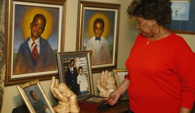 In this Tuesday, Feb. 14, 2017 photo, Jannie Coverdale looks over photos of her two grandsons, Aaron Coverdale, left, and Elijah Coverdale, right, who both died in the 1995 Oklahoma City bombing, in her home in Oklahoma City. Coverdale said she sees a terrorism risk from potential attackers who sneak into the U.S. from abroad. (AP Photo/Sue Ogrocki)