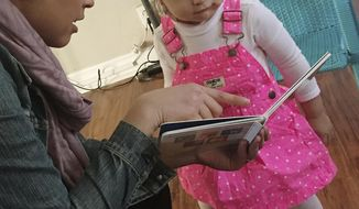 In this Jan. 11, 2016 photo, caseworker Stephanie Taveras, left, reads a book with 20-month-old Gracey Niebla, right, at the child's home in Providence, R.I. The city is in the third year of its effort to boost language skills for children from low-income families by equipping them with audio recorders that count every word they hear. During home visits, social workers go over the word counts with parents and suggest tips to boost children's language skills. (AP Photo/Matt O'Brien)