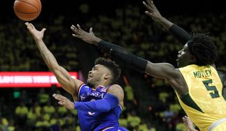 Kansas guard Frank Mason III, left, goes up for a shot after getting past Baylor forward Johnathan Motley (5) in the first half of an NCAA college basketball game, Saturday, Feb. 18, 2017, in Waco, Texas. (AP Photo/Tony Gutierrez)