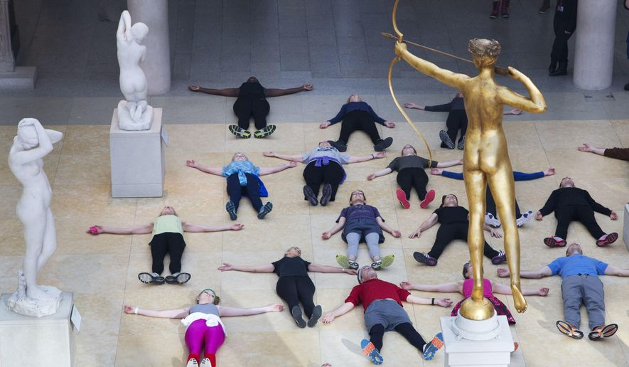 In this Feb. 10, 2017 photo, an exercise group lies down at the feet of a bronze statue of Diana, the Roman goddess of the hunt, after a workout at the Metropolitan Museum of Art in New York. The museum has been hosting lively workout sessions amid its prized masterpieces. (AP Photo/Mark Lennihan)