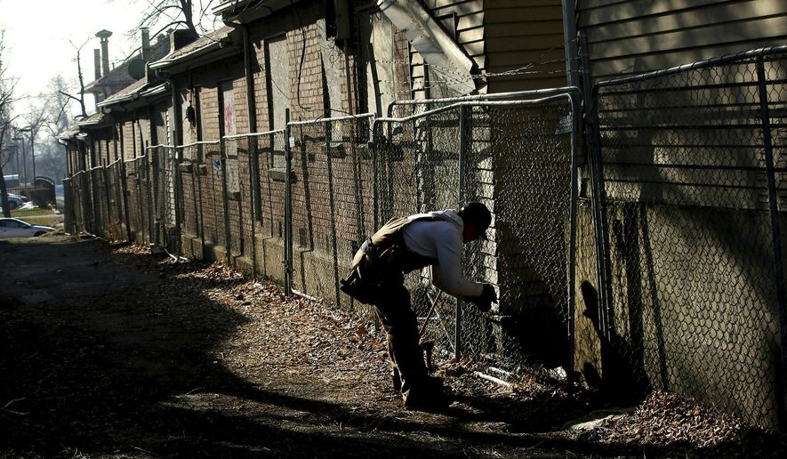 In this Jan. 18, 2017 photo, repairman Benjamin Florentino Hernandez fixes the fencing that surrounds the properties at 647-653 E. 100 South in Salt Lake City on Wednesday, Jan. 18, 2017. The buildings are protected under historic district rules, but are homes to vagrants with no evident economic value. They have been abandoned now for years, after the city condemned the structures. They are boarded up, but homeless people and drug addicts will tear down the boards about once a week and squat in the buildings. (Laura Seitz/The Deseret News via AP)