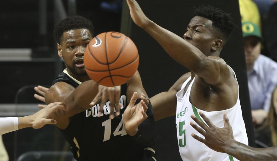 Colorado's Tory Miller passes the ball pressure from Oregon's Kavell Bigby-Williams during the first half of an NCAA college basketball game Saturday, Feb. 18, 2017, in Eugene, Ore. (AP Photo/Chris Pietsch)