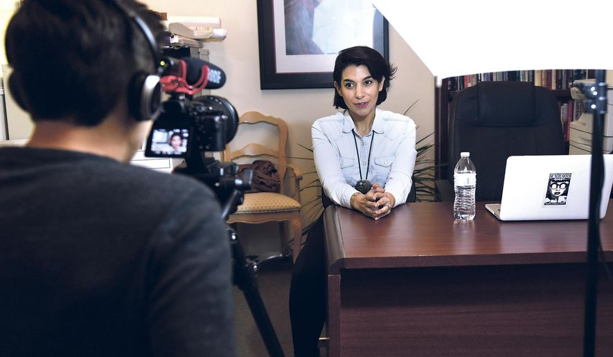 "In a Feb. 9, 2017 photo, Henry Valdez films Marina Rossi, who playes Andrea in 'Bad Broker' during their ""pitch"" video for Indiegogo to solicit $5,000 in open source funding in the real estate office they use as a set for their web series in Santa Fe, N.M. (Clyde Mueller/Santa Fe New Mexican via AP)"