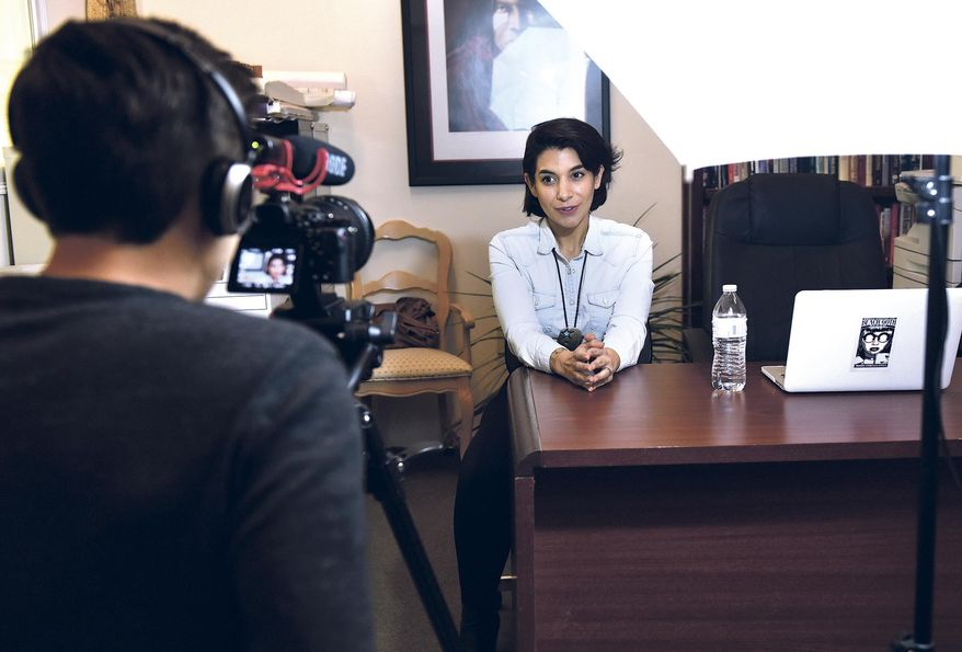 """In a Feb. 9, 2017 photo, Henry Valdez films Marina Rossi, who playes Andrea in 'Bad Broker' during their """"pitch"""" video for Indiegogo to solicit $5,000 in open source funding in the real estate office they use as a set for their web series in Santa Fe, N.M. (Clyde Mueller/Santa Fe New Mexican via AP)"""