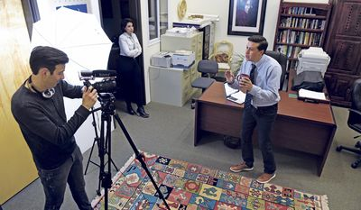 """In a Feb. 9, 2017 photo, Henry Valdez plays Brad, Marina Rossi who plays Andrea and Michael Estrada plays Joey, cast members of 'Bad Broker' film their """"pitch"""" video for Indiegogo in Santa Fe, N.M., to solicit $5,000 in open source funding in the real estate office they use as a set for their web series. (Clyde Mueller/Santa Fe New Mexican via AP)"""