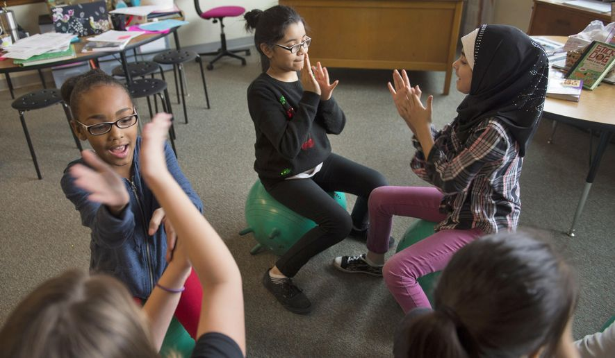In this Friday, Jan. 13, 2017 photo, from left, Tashaiyah Dyer-Turner,  Brooke Roldan and Fatma Al-Asady have fun during free time in Mackenzie Wylie's fourth grade class at Saratoga Elementary School. In the weeks Wylie's had stability balls in her classroom at Saratoga Elementary, she's noticed good things. Her fourth-graders, she said, are more focused on the task at hand. The balls are providing a way for students who have a hard time sitting still to work off excess energy. (Jake Crandall/The Journal-Star via AP)