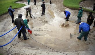 Groundskeepers work to remove water from a bunker on the 14th hole before the second round of the Genesis Open golf tournament at Riviera Country Club Saturday, Feb. 18, 2017, in the Pacific Palisades area of Los Angeles. (AP Photo/Ryan Kang)
