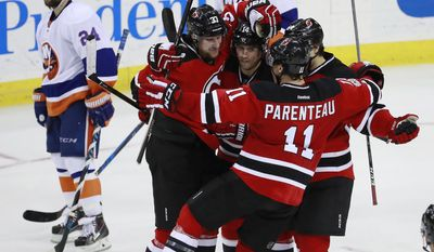 New York Islanders players Stephen Gionta, top left, and Dennis Seidenberg, top, of Germany, skate by as Devils players, from left, Pavel Zacha, of the Czech Republic, Adam Henrique, PA Parenteau and Joseph Blandisi celebrate a goal by Zacha during the third period of an NHL hockey game, Saturday, Feb. 18, 2017, in Newark, N.J. (AP Photo/Julio Cortez)