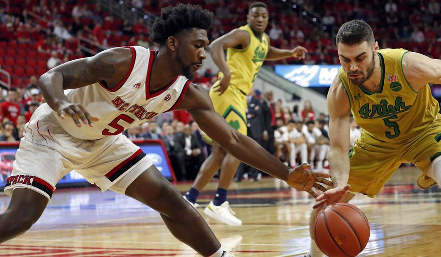 North Carolina State's Darius Hicks, left, struggles with Notre Dame's Matt Farrell to control the ball during the first half of an NCAA college basketball game in Raleigh, N.C., Saturday, Feb. 18, 2017. (AP Photo/Karl B DeBlaker)