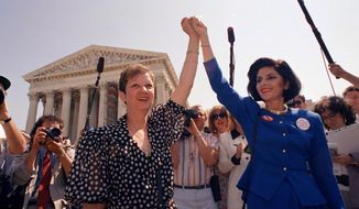FILE - In this April 26, 1989 file photo, Norma McCorvey, Jane Roe in the 1973 court case, left, and her attorney Gloria Allred hold hands as they leave the Supreme Court building in Washington after sitting in while the court listened to arguments in a Missouri abortion case.   McCorvey died at an assisted living center in Katy, Texas on Saturday, Feb. 18, 2017, said journalist Joshua Prager, who is working on a book about McCorvey and was with her and her family when she died. He said she died of heart failure.(AP Photo/J. Scott Applewhite, File)