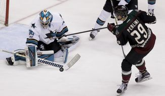 San Jose Sharks goalie Aaron Dell, left, blocks a shot by Arizona Coyotes left wing Brendan Perlini during the second period of an NHL hockey game in Glendale, Ariz., Saturday, Feb. 18, 2017. (AP Photo/Chris Carlson)