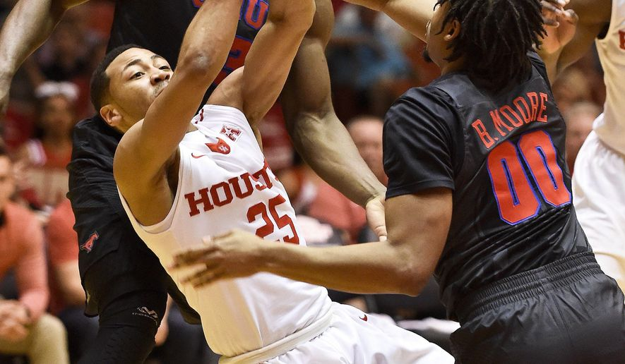 Houston guard Galen Robinson Jr., left, passes over SMU forward Ben Moore in the first half of an NCAA college basketball game, Saturday, Feb. 18, 2017, in Houston. (AP Photo/Eric Christian Smith)