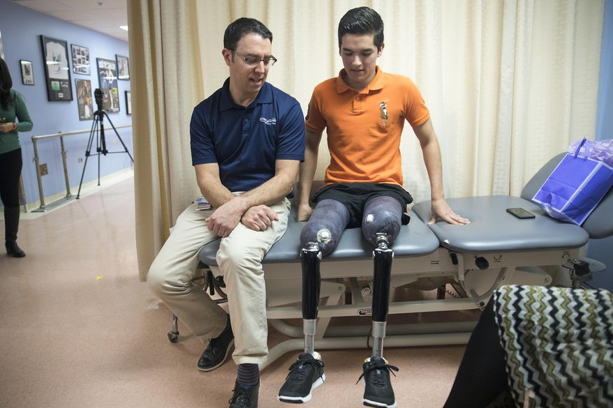 In this Monday, Feb 13, 2017 photo, prosthetist David Rotter, left, of Scheck & Siress, coaches Vidal Lopez before he takes a walk down the hallway in his new prosthetic legs at the University of Illinois at Chicago Hospital, in the Near West Side neighborhood. Heather Abbott, a survivor of the Boston Marathon bombing and founder of The Heather Abbott Foundation, teamed up with Scheck & Siress, a Chicago based prosthetic firm to provide Lopez with new customizable prosthetic legs. Vidal was born in Chicago but grew up in Mexico. A car crash involving a tractor trailer in July 2016, left him without his legs. He wrote to the Heather Abbott Foundation with hopes to receive a grant to help him pay for the prosthetic legs that he needed. Heather was touched by his story and decided to provide Vidal with the financial support he needed to secure his future. (Alyssa Pointer/Chicago Tribune via AP)