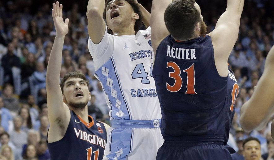 North Carolina's Justin Jackson (44) drives between Virginia's Ty Jerome (11) and Jarred Reuter (31) during the first half of an NCAA college basketball game in Chapel Hill, N.C., Saturday, Feb. 18, 2017. (AP Photo/Gerry Broome)