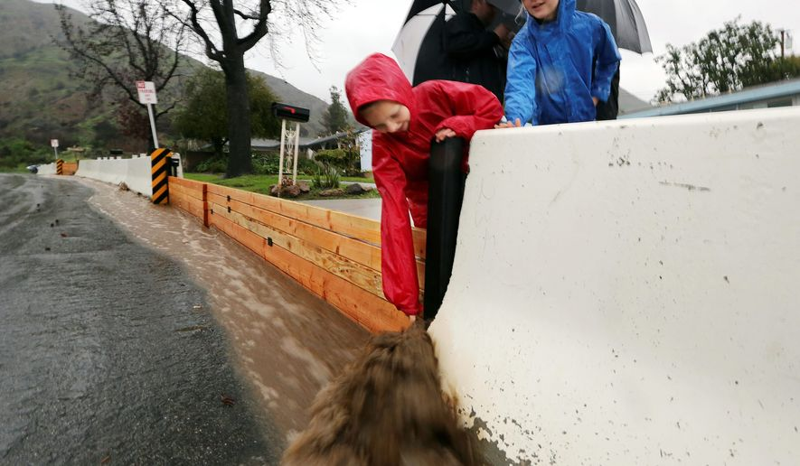 Ethan Finlay tests muddy water flowing down a road as K-rails and boards protect homes in Duarte, California. The state faces a new round of wet weather Sunday through Tuesday. (Associated Press photographs)