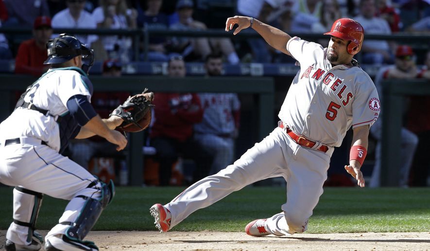 FILE - In this Sept. 4, 2016, file photo, Los Angeles Angels' Albert Pujols (5) slides into a tag by Seattle Mariners' Chris Iannetta at home to end the eighth inning of a baseball game in Seattle. Pujols is hard at work to make sure his return from foot surgery stays on schedule. (AP Photo/Elaine Thompson, File)