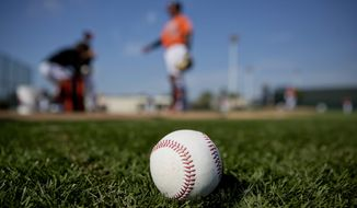 A ball sits on the field as Baltimore Orioles players work out during baseball spring training in Sarasota, Fla., Wednesday, Feb. 15, 2017. (AP Photo/David Goldman)